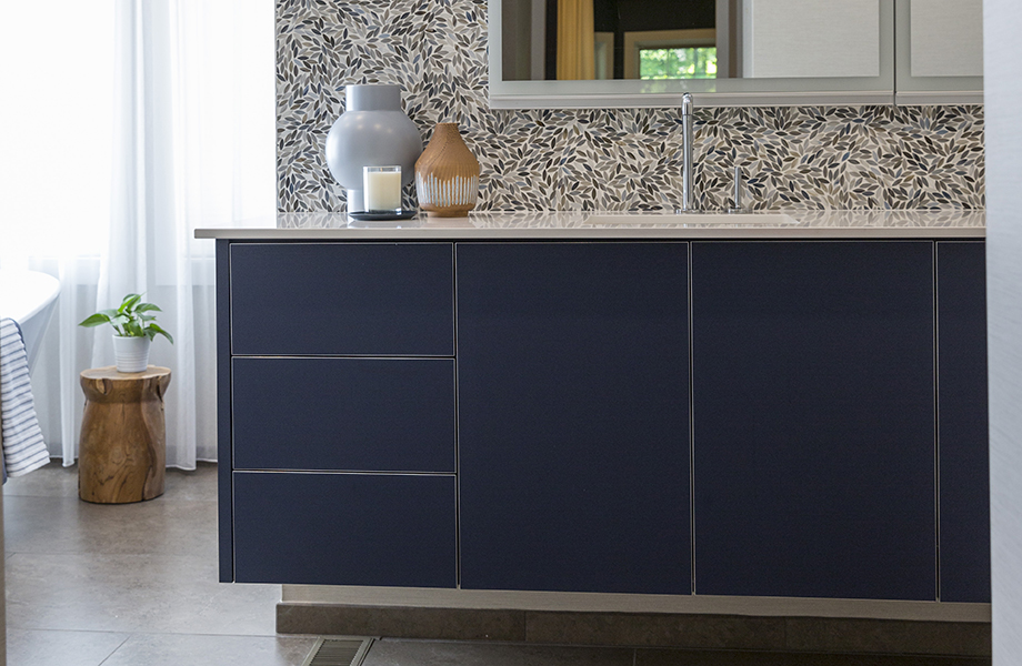 FENIX Evolo Design gray bathroom cabinetry with white countertops, abstract wallpaper, large mirror and vases