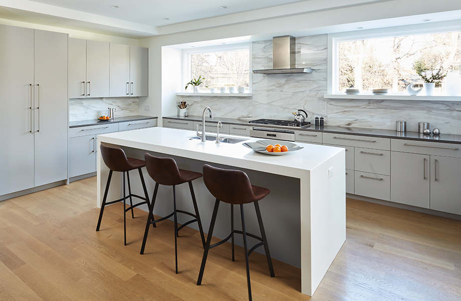 Full kitchen with waterfall island and stools with Grigio Efeso cabinetry and Grigio Antrim feature wall