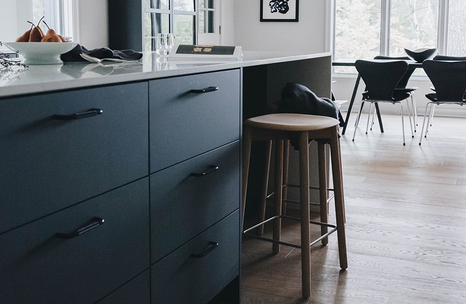 Gray Nordic Design cabinetry with white countertops, bar stool and table with a set of chairs