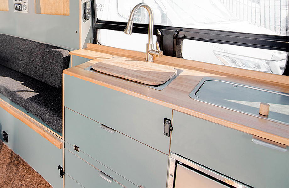 Texino campervan kitchen with light gray FENIX cabinetry, wooden countertops and sink