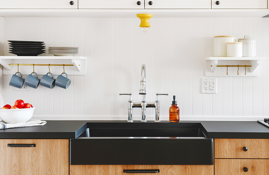 Modern kitchen with wooden cabinetry, black countertops and sink with kitchen accessories